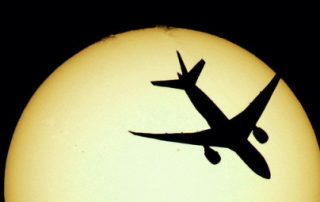 Aircraft flying across disc of the sun